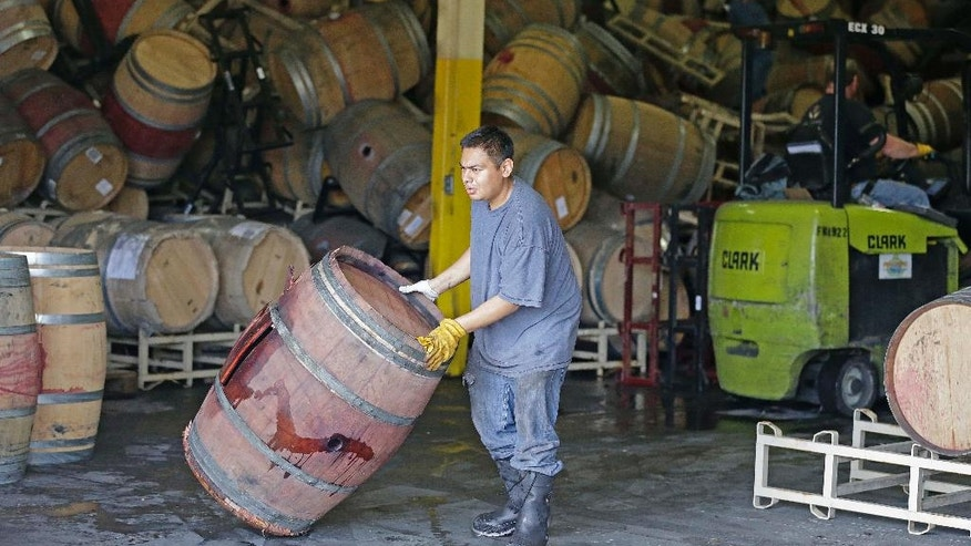 A worker removes an earthquake-damaged wine barrel from a barrel storage facility Monday, Aug. 25, 2014, in Napa, Calif. A powerful earthquake that struck the heart of California's wine country caught many people sound asleep, sending dressers, mirrors and pictures crashing down around them and toppling wine bottles in vineyards around the region. The magnitude-6.0 quake struck at 3:20 a.m. PDT Sunday near the city of Napa. (AP Photo/Eric Risberg)
