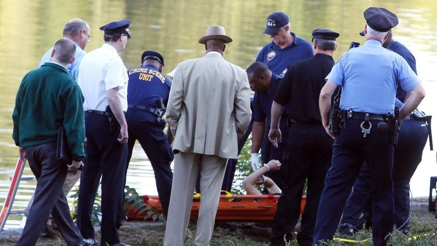 Philadelphia police and other law enforcement officials view a body pulled from the Schuylkill River in Fairmount Park in Philadelphia, Wednesday, Aug. 27, 2014.  The bound bodies of two people were found in the river Wednesday, and a third man who said he managed to free himself is being treated at a hospital for stab wounds, police said. (AP Photo/Jacqueline Larma)