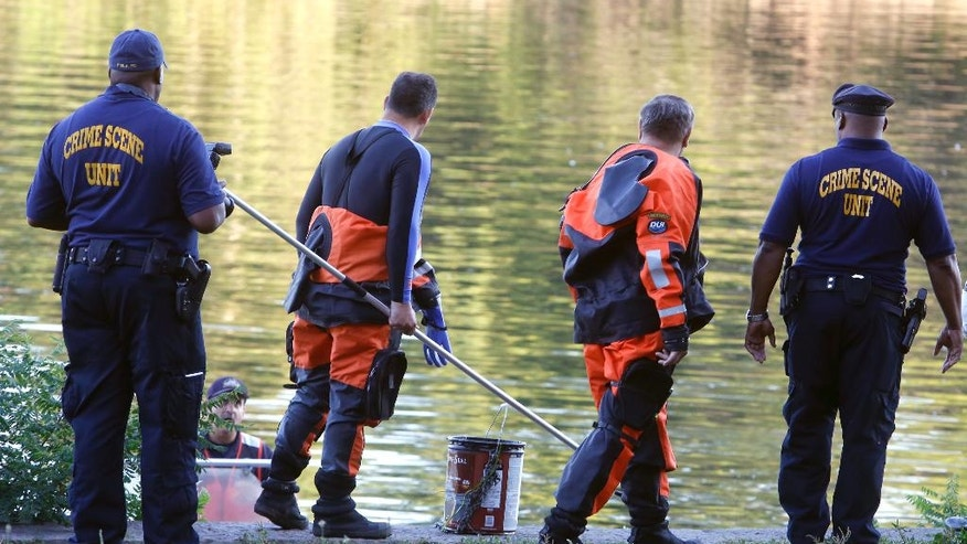 Philadelphia police bring ashore a bucket from the Schuylkill River in Fairmount Park as they investigate, in Philadelphia, Wednesday, Aug. 27, 2014.  The bound bodies of two people were found in the river Wednesday, and a third man who said he managed to free himself is being treated at a hospital for stab wounds, police said. (AP Photo/Jacqueline Larma)