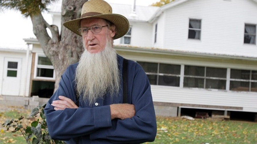 FILE - In this Monday, Oct. 10, 2011 file photo, Sam Mullet stands in front of his Bergholz, Ohio, home. An appeals court on Wednesday, Aug. 27, 2014  overturned the hate-crime convictions of 16 Amish in beard- and hair-cutting attacks on fellow members of their faith in Ohio. The attacks were in apparent retaliation against Amish who had defied or denounced the authoritarian style of leader Mullet. (AP Photo/Amy Sancetta, File)