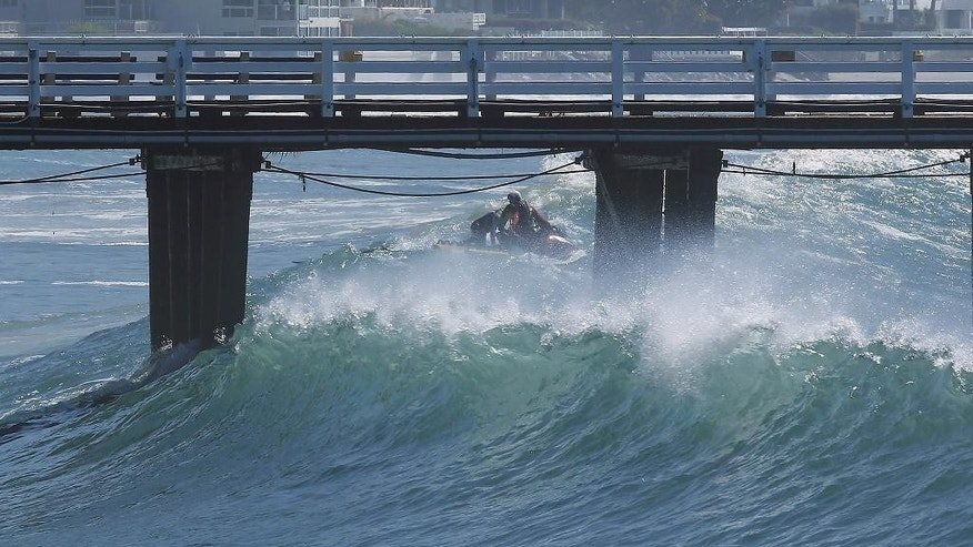 An unidentified surfer gets assistance from a Los Angeles County lifeguard on a watercraft, as heavy waves crash against the pier in Malibu, Calif., Wednesday, Aug. 27, 2014. Southern California beachgoers experienced much higher than normal surf, brought by Hurricane Marie spinning off the coast of Mexico. (AP Photo/Damian Dovarganes)