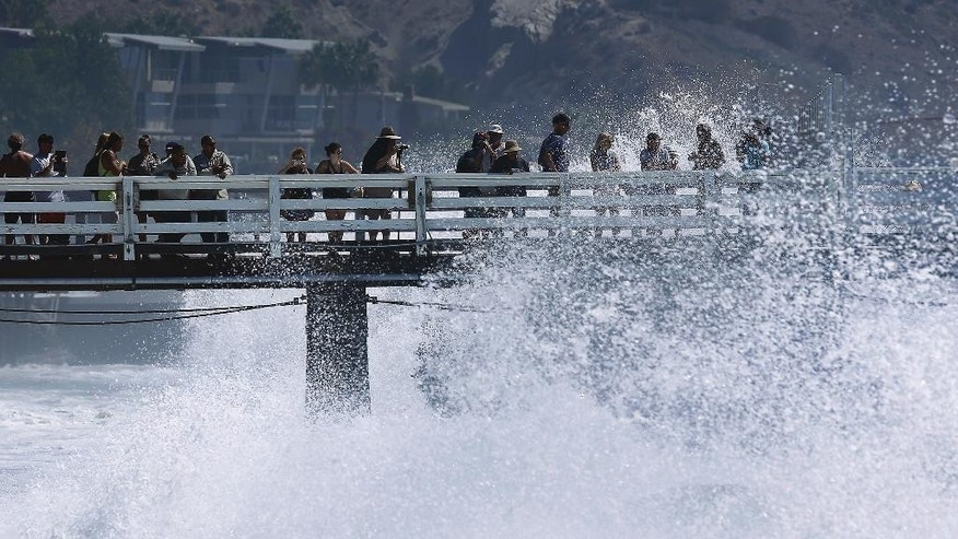 Surf watchers are splashed at the pier in Malibu, Calif., Wednesday, Aug. 27, 2014. Southern California beachgoers experienced much higher than normal surf, brought by Hurricane Marie spinning off the coast of Mexico. (AP Photo/Damian Dovarganes)
