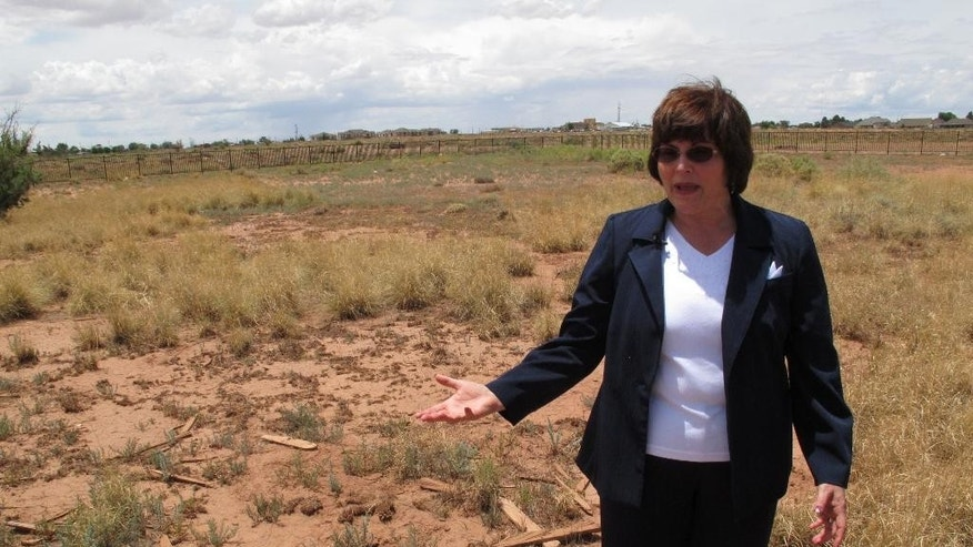 This July 9, 2014 photo shows Gail Sadler standing amid broken crosses in a pauper's grave in Winslow, Arizona.  The local historic preservation commissioner has made it her mission to unearth the identities of roughly 600 people buried there and help their descendants reconnect with a lost part of their history. (AP Photo/Felicia Fonseca)