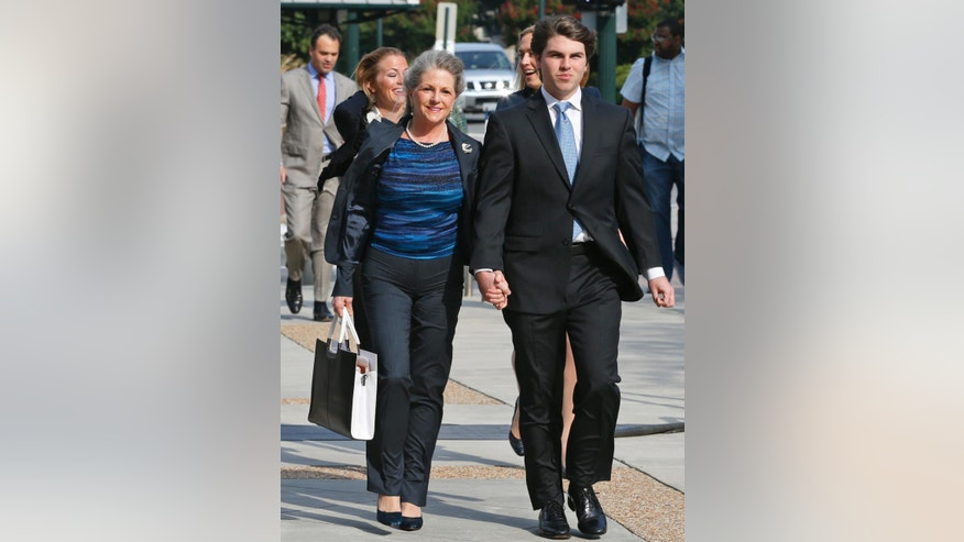 Former Virginia first lady Maureen McDonnell holds hands with her son Bobby as they arrive at federal court in Richmond, Va., Thursday, Aug. 28, 2014.  The prosecution in the McDonnell corruption case begins its rebuttal today. (AP Photo/Steve Helber)