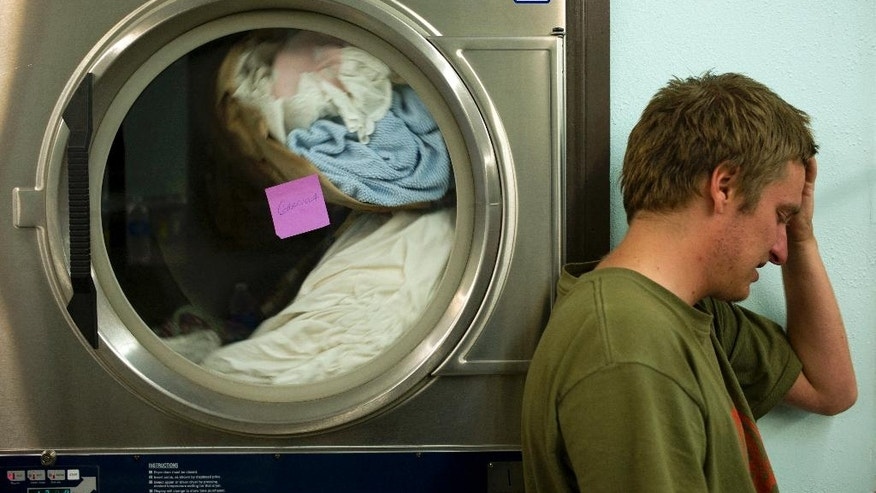 In this Aug. 13, 2014, photo, Justin Gavin, 21, who is homeless, leans against a dryer while getting his laundry done for free during a Laundry Love event in Huntington Beach, Calif. Laundry Love is a growing faith-driven movement that helps people change their lives by letting them change into clean clothes. The organization aims to give back in a simple yet innovative way by partnering with local laundromats and helping those who are homeless or struggling financially by doing their laundry for free. (AP Photo/Jae C. Hong)