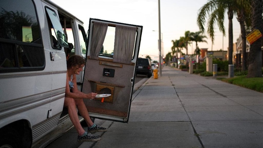In this Aug. 13, 2014, photo, Vicki Bennett, a 50-year-old homeless woman who lives in her van, eats her dinner while waiting to do her laundry outside a laundromat during a Laundry Love event in Huntington Beach, Calif. Laundry Love is a growing faith-driven movement that helps people change their lives by letting them change into clean clothes. The organization partners with local laundromats and helps those who are homeless or struggling financially by doing their laundry for free. (AP Photo/Jae C. Hong)
