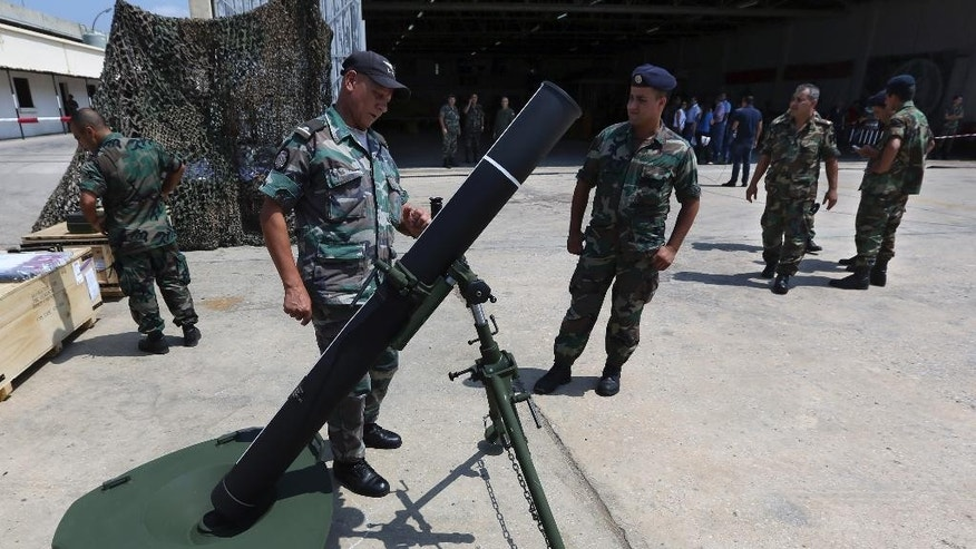 Lebanese army soldiers look at a mortar at the Rafik Hariri International Airport in Beirut, Lebanon, Friday, Aug. 29, 2014. The United States has delivered the first shipment of weapons to Lebanon to help bolster its military as it faces a growing threat from Islamic militants amid the fallout from neighboring Syria's civil war. (AP Photo/Bilal Hussein)