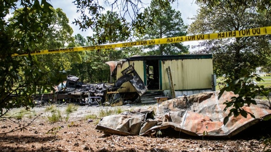 This Saturday, Aug. 30, 2014 photo shows the burned remains of a mobile home in Garland, N.C. An early Saturday fire killed six people inside, authorities said. (AP Photo/The Fayetteville Observer, James Robinson)