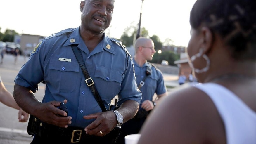 FILE -In this Aug. 19, 2014 file photo, Missouri Highway Patrol Capt. Ron Johnson meets with residents while walking the streets of Ferguson, Mo. Under Johnson's measured guidance, calm has been restored in Ferguson as the violent protests have ended, shops and restaurants along West Florissant are slowly getting back to business. (AP Photo/Jeff Roberson, File)