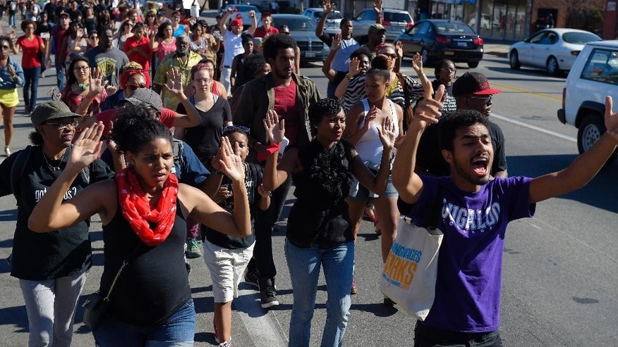 FILE - In this Aug. 14, 2014 file photo, protesters hold their hands up as they walk in the middle of Crenshaw Blvd. to protest the shooting of an unarmed man in Ferguson, Mo., and of other victims of police shootings in Los Angeles. Details may differ, circumstances of their deaths may remain unknown, but the outrage that erupted after the Aug. 9 fatal shooting of the unarmed, black 18-year-old by a white officer in Ferguson, Missouri, has become a rallying cry in protests over police killings across the nation. (AP Photo/Mark J. Terrill, File)