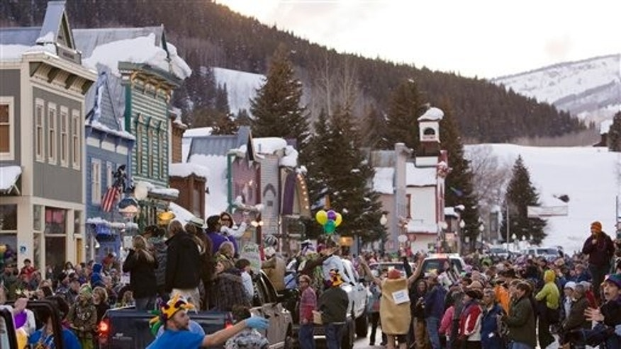 In this Feb. 24, 2009, file photo, a crowd gathers on Elk Avenue in Crested Butte, Colo., during a Mardi Gras parade celebration. Some people in normally laid back Crested Butte are not up for a secretive Bud Light plan to paint their mountain town blue and turn it into a fantasy town for an ad campaign. (AP Photo/Nathan Bilow, File)