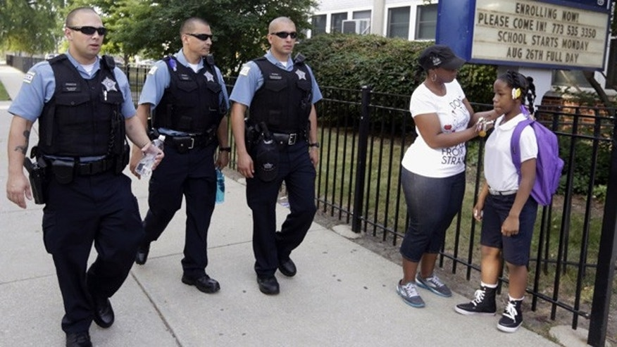 FILE - In this Aug. 26. 2013, file photo, Chicago Police patrol the neighborhood at Gresham Elementary School on the first day of classes in Chicago. (AP Photos/M. Spencer Green, File)