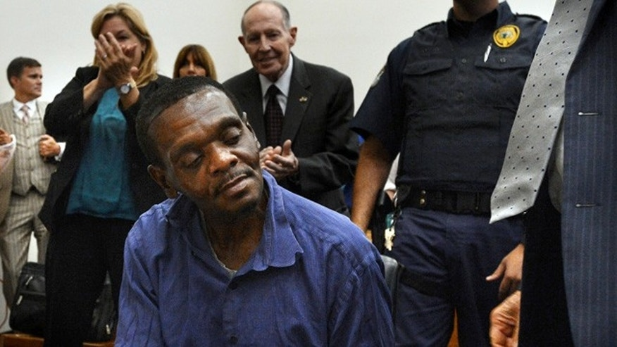 September 2, 2014: Henry McCollum sits quietly as thunderous applause rings out around him in a Robeson County courtroom in Lumberton, N.C. On Tuesday, a judge overturned the convictions of McCollum, 50, and Leon Brown, 46, in the 1983 rape and murder of an 11-year-old girl, citing DNA evidence that they are innocent. (AP Photo/The News & Observer, Chuck Liddy)
