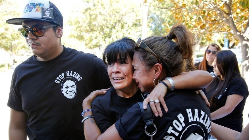 Family members of late Armando Villa, from left: Joshua Castaneda, his mother Martha Castaneda, and aunt, Maria Castaneda react as California State University, Northridge, CSUN president Dr. Dianne Harrison, not seen, reads a statement regarding Pi Kappa Phi Fraternity activities that lead to the death of CSUN student Armando Villa, during a news conference at the CSUN campus in Northridge, Calif., on Friday, Sept. 5, 2014. Villa died during a fraternity-sponsored hike in the Angeles National Forest. (AP Photo/Damian Dovarganes)