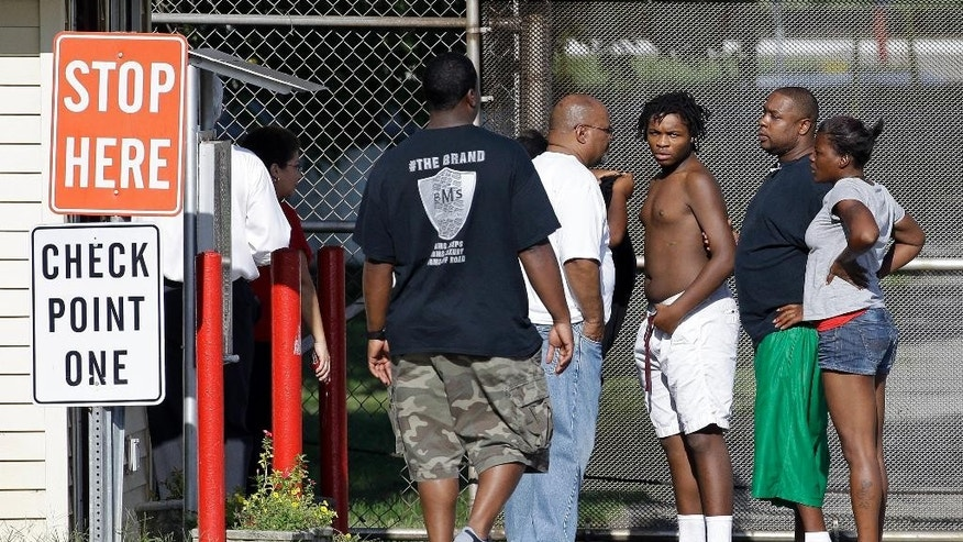 One of 32 escaped teenagers, third from right, is turned in by family members, according to a Tennessee Department of Children's Services spokesman, in front of the Woodland Hills Youth Development Center Tuesday, Sept. 2, 2014, in Nashville, Tenn. The teenagers, ages 14 to 19, escaped from the facility Monday night. (AP Photo/Mark Humphrey)