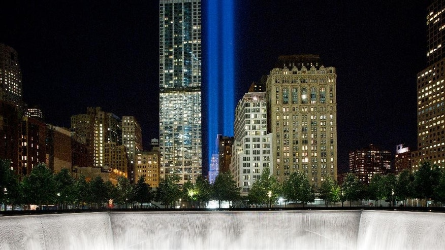 The Tribute in Light rises behind buildings adjacent to the World Trade Center complex and a reflecting pool at the National September 11 Memorial, Monday, Sept. 8, 2014, in New York. The tribute, an art installation of 88 searchlights aiming skyward in two columns, is a remembrance of the Sept. 11, 2001, attacks. (AP Photo/Mark Lennihan)