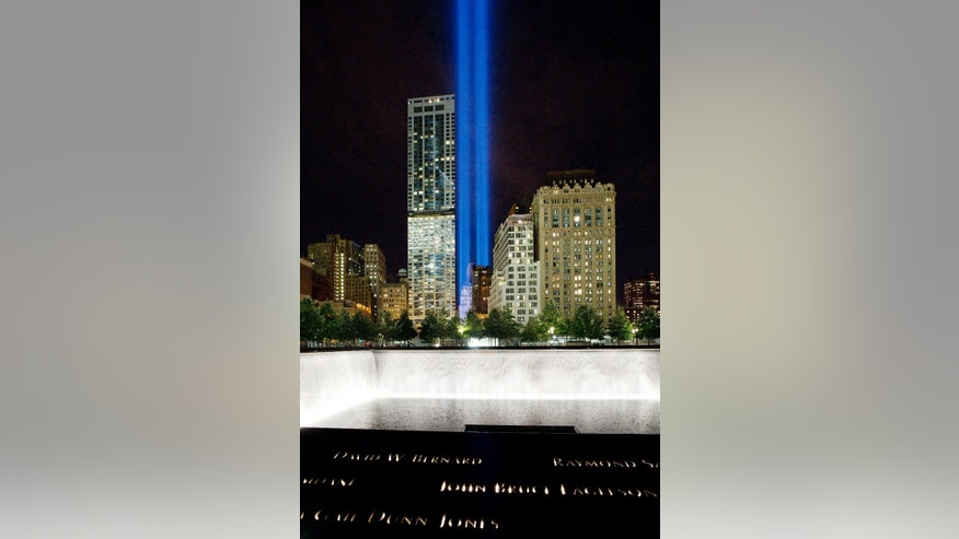 CORRECTS LOCATION OF THE LIGHT TO ADJACENT TO THE WTC COMPLEX, NOT 1 WTC - The Tribute in Light rises behind buildings adjacent to the World Trade Center complex and a reflecting pool at the National September 11 Memorial, Monday, Sept. 8, 2014, in New York. The tribute, an art installation of 88 searchlights aiming skyward in two columns, is a remembrance of the Sept. 11, 2001, attacks. (AP Photo/Mark Lennihan)