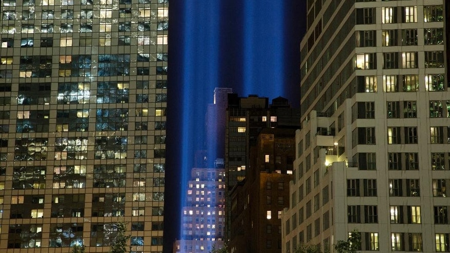 CORRECTS LOCATION OF THE LIGHT TO ADJACENT TO THE WTC COMPLEX, NOT 1 WTC - The Tribute in Light rises behind buildings adjacent to the World Trade Center complex, Monday, Sept. 8, 2014, in New York. The tribute, an art installation of 88 searchlights aiming skyward in two columns, is a remembrance of the Sept. 11, 2001, attacks. (AP Photo/Mark Lennihan)