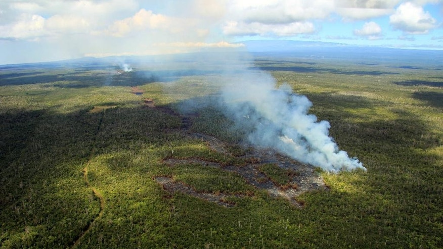 In this Sept. 6, 2014 aerial photo released by the U.S. Geological Survey, lava advances from the Kilauea volcano in Pahoa, Hawaii. Lava issued from several spots along a deep ground crack earlier this week, as shown by the distinct fingers of lava making up the flow front. The thick smoke plumes show the flow front moving downslope towards the north. Lava from one of the world's most active volcanos has been advancing at a slower pace the past few days and is now moving parallel to a sparsely populated subdivision on Hawaii's Big Island. Hawaii County Civil Defense Director Darryl Oliveira says the lava from Kilauea volcano is still at least a mile away from any homes in Kaohe Homesteads. (AP Photo/Tim Orr, U.S. Geological Survey)