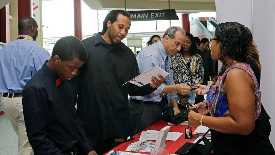 In this photo taken Tuesday, Aug. 19, 2014, job seeker Stephen Watson, of Fort Lauderdale, second from left, reviews the job qualifications during a job fair in Sunrise. Fla. The Labor Department reports on job openings and labor turnover in July on Tuesday, Sept. 9, 2014. (AP Photo/Alan Diaz)