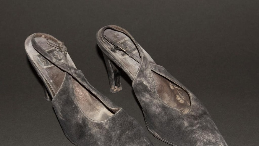 """This July 29, 2014 photo provided by the National September 11 Memorial and Museum, shows a pair of high-heel shoes worn by JoAnne """"JoJo"""" Capestro while descending 87 floors of stairs to escape a World Trade center tower on Sept. 11, 2001. The shoes are among the clothes, wallets, helmets, and other personal effects donated to the museum by survivors and those who worked at the site in the attacks' aftermath. (AP Photo/National September Memorial and Museum, John D Childs)"""