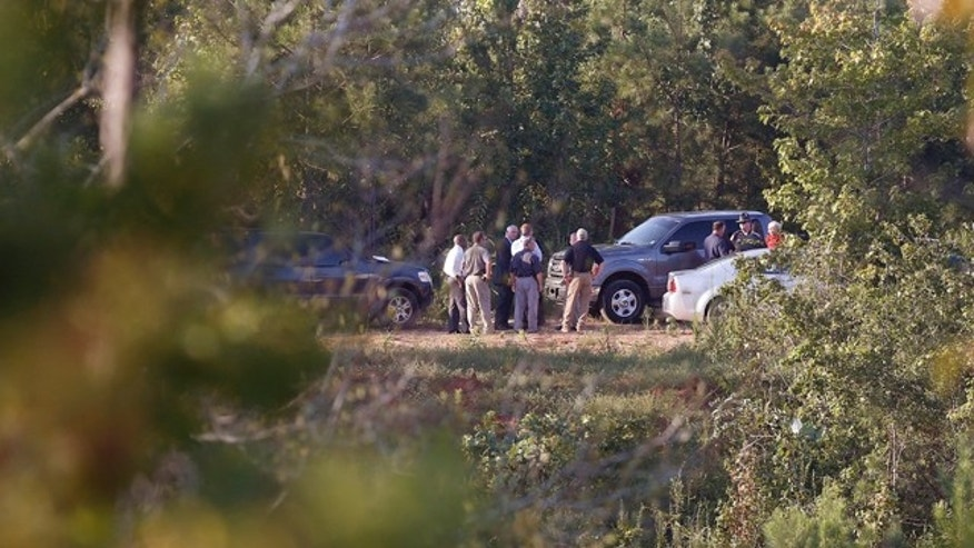 September 9, 2014: Authorities gather in a field surrounded by trees in Camden, Ala, where a district attorney says the bodies of five children missing from South Carolina have been found. (AP Photo/Brynn Anderson)