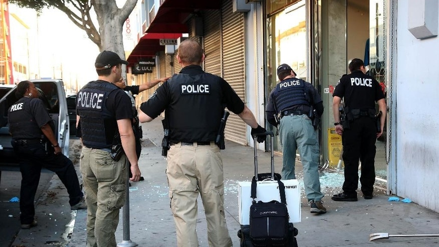 Law enforcement agents stand outside a clothing store during a raid in the Los Angeles Fashion District Wednesday, Sept. 10, 2014.  U.S. agents raided dozens of businesses in the fashion district of Los Angeles early Wednesday as part of an investigation into suspected money laundering done for Mexican drug cartels. (AP Photo/ Nick Ut )