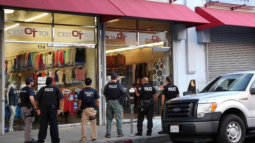 Law enforcement agents stand outside a clothing store after a raid in the Los Angeles Fashion District Wednesday, Sept. 10, 2014.  U.S. agents raided dozens of businesses in the fashion district of Los Angeles early Wednesday as part of an investigation into suspected money laundering done for Mexican drug cartels. (AP Photo/ Nick Ut )