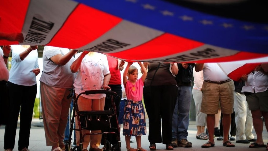 Sarah Kowalczyk, 6, from Lake Village, Indiana, holds a giant flag while participating in a sunset memorial service at the Flight 93 National Memorial on Wednesday, September 10, 2014. (AP Photo/Gene J. Puskar)