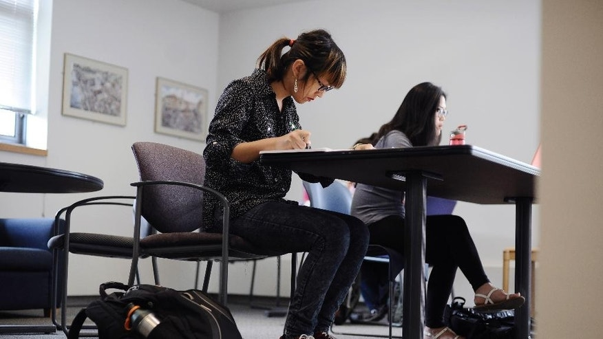 In this Sept. 9, 2014 photo, transgender student Calliope Wong, left, studies before class at the University of Connecticut in Storrs, Conn. Women's colleges are revisiting policies around enrolling transgender students. (AP Photo/Jessica Hill)