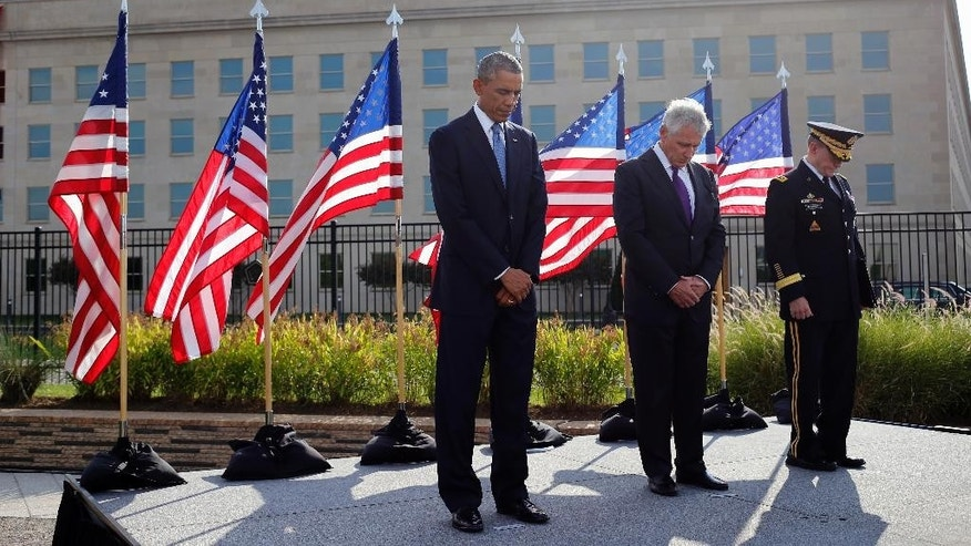 From left, President Barack Obama, Defense Secretary Chuck Hagel, and Joint Chiefs Chairman Gen. Martin Dempsey stand at the Pentagon, Thursday, Sept. 11, 2014, during a ceremony to mark the 13th anniversary of the 9/11 attacks. (AP Photo/Charles Dharapak)