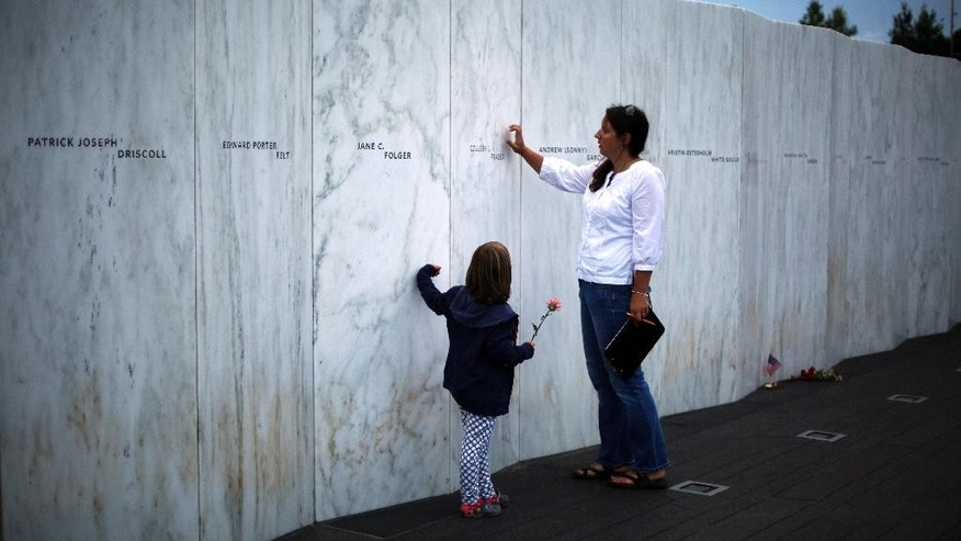 Visitors to the Flight 93 National Memorial in Shanksville, Pa., on Wednesday, Sept. 10, 2014, touch the Wall of Names. The memorial marks the spot where United Airlines Flight 93 crashed 13 years ago in a reclaimed strip mine some 75 miles southeast of Pittsburgh after passengers fought back against hijackers. (AP Photo/Gene J. Puskar)