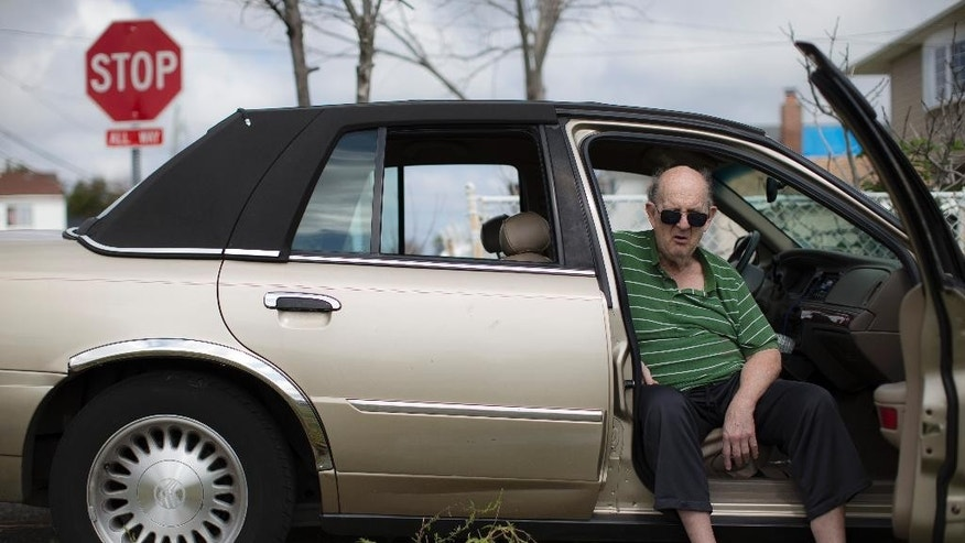 In this Sept. 5, 2014 photo, Albert Silberman sits in a car outside his home that was destroyed by Superstorm Sandy in Lindenhurst, N.Y. After receiving nearly $17,000 in assistance from FEMA, the agency is demanding a return on the funds. (AP Photo/John Minchillo)
