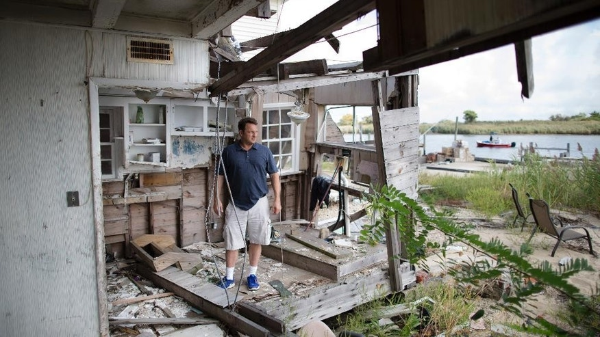 In this Sept. 5, 2014 photo, Gary Silberman stands for a picture as he guides reporters on a tour of his parent's home that was destroyed by Superstorm Sandy, in Lindenhurst, N.Y. After Silberman received nearly $17,000 in assistance from FEMA, the agency is demanding a return on the funds. (AP Photo/John Minchillo)