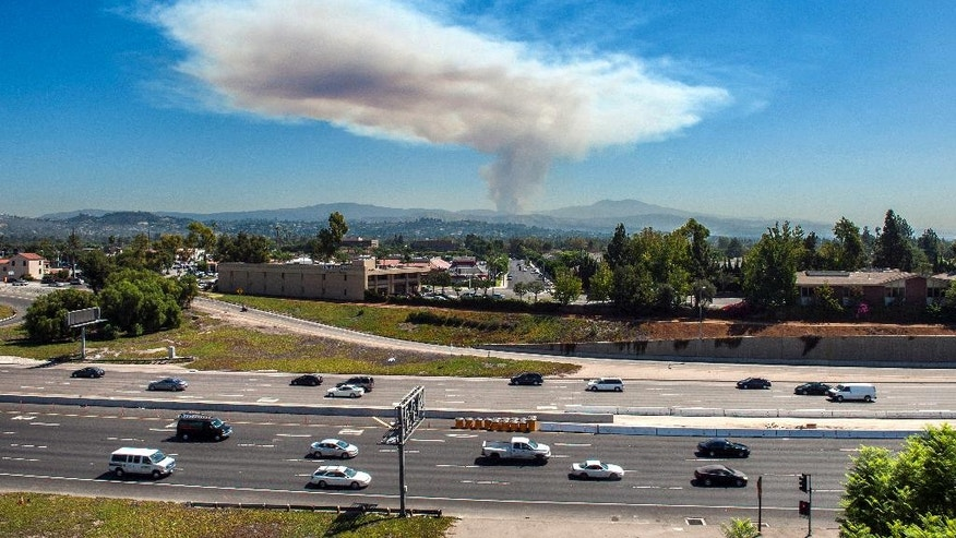 A plume of smoke rises into the sky as a wildfire burns in the Cleveland National Forest in eastern Orange County, while traffic moves along a freeway through Tustin, Calif. on Friday, Sept. 12, 2014. (AP Photo/Orange County Register, Mark Rightmire)