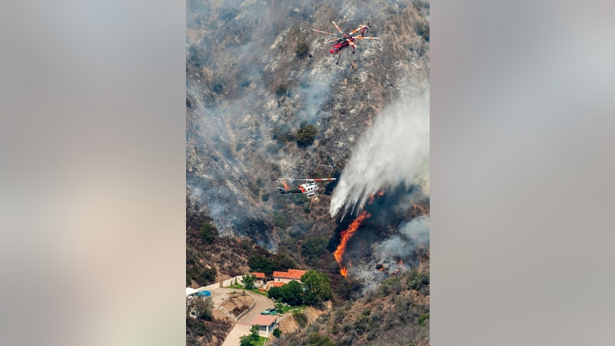 Helicopters drop water on a wildfire burning near a home in Silverado Canyon in eastern Orange County on Friday, Sept. 12, 2014. (AP Photo/Orange County Register, Mark Rightmire)