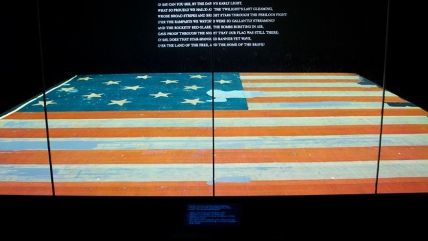 "Sept. 5, 2014: This photo shows the Smithsonian's National Museum of American History in Washington exhibit of the flag that inspired the national anthem ""Star-Spangled Banner."" Years ago parts of the flag were snipped off and handed out as mementos and the Smithsonian has been reacquiring some of those fragments and adding to their collection."