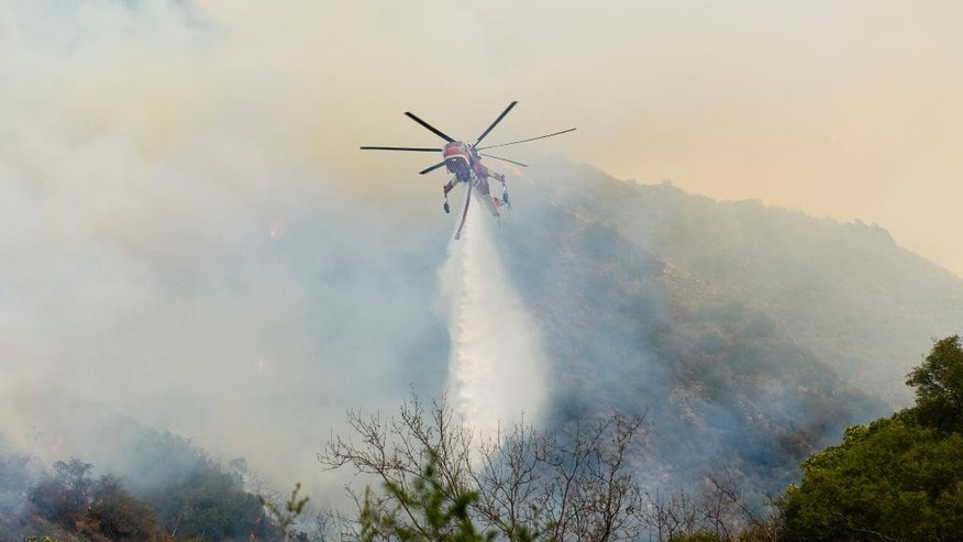 An Orange County Fire Authority helicopter drops a load of water on a brush fire in Silverado Canyon in Orange County, Calif. on Friday, Sept. 12, 2014. (AP Photo/Orange County Register, Sam Gangwer)