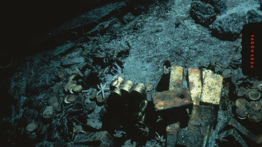 FILE - This 1989 file photo shows gold bars and coins from the S.S. Central America, a mail steamship, which sunk in a hurricane in 1857, about 160 miles off the North Carolina coast. Columbus-America Discovery Group, owned by fugitive treasure hunter Tommy Thompson, argues that it has the exclusive rights to the treasure from the shipwreck. (AP Photo/File)