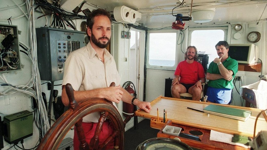 In this Aug. 29,1991 photo, Tommy Thompson, left, stands at the helm of the Arctic Explorer as Bob Evans, center, and Barry Schatz look on in Norfolk, Va. Thompson led a group that recovered millions of dollars worth of sunken treasure only to end up involved in court cases brought by dozens of insurance companies laying claim to the treasure. (AP Photo/Columbus Dispatch, Doral Chenoweth III)