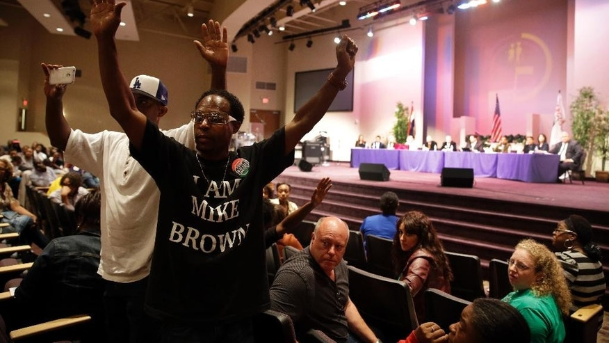 FILE - In this Sept. 9, 2014 file photo, Marurice Brown raises his arms during a public comments portion of a meeting of the Ferguson City Council, in Ferguson, Mo. The meeting was the first for the city council after the fatal shooting of Michael Brown by a city police officer.   Political participation is increasing on the national level for blacks and Hispanics. On the local level, voting continues to be a struggle, as it is in this St. Louis suburb.   (AP Photo/Jeff Roberson, File)