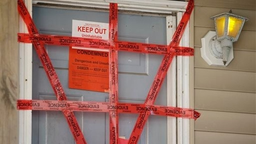 "Sept. 12, 2014: Both ""condemned"" and ""keep out"" signs are attached behind police tape to the front door of a house where a Massachusetts prosecutor said the bodies of three infants were found."