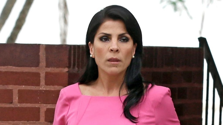 FILE - In this Nov. 13, 2012, file photo, Jill Kelley leaves her home in Tampa, Fla.   U.S. District Judge Amy Berman Jackson says Jill Kelley can press her claim that the FBI and Defense Department violated her privacy when officials allegedly leaked information about her to the news media. Berman also tossed out more than a dozen other claims of government wrongdoing.   (AP Photo/Chris O'Meara, File)