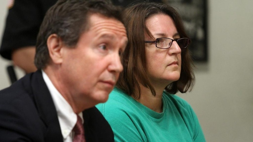 Michelle Lodzinski sits beside her attorney Gerald Krovatin during her arraignment  in State Superior Court, Tuesday, Sept. 16, 2014, in New Brunswick, N.J. Lodzinski, is charged in the 1991 death of her 5-year-old son, Timothy Wiltsey.  Lodzinski, 46, has been in custody since her arrest August 7. She's was extradited to New Jersey on Friday and is being held in the county jail on $2 million bail.  (AP Photo/ Home News Tribune, Jason Towlen, Pool)