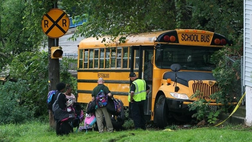 Student book bags are removed from the scene of an accident on Tuesday, Sept. 16, 2014, in Akron, Ohio. Police say a school bus driver was killed when the bus rolled over her during an evacuation drill outside an Akron charter school. A police spokesman says the 51-year-old driver sacrificed her life to save a 10-year-old girl who was about to jump out of the emergency exit at the back of the bus Tuesday morning.  (AP Photo/Akron Beacon Journal, Ed Suba Jr)  MANDATORY CREDIT