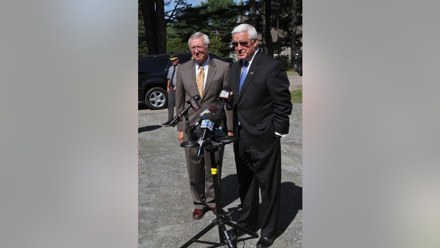 Pennsylvania Gov. Tom Corbett, right, speaks to the press at the Blooming Grove Baptist Church in Pike County, Pa., Monday, Sept. 15, 2014 about the shooting Friday night that took the life of a Pennsylvania State Police trooper and critically injured another.  Corbett said investigators won't rest until they capture the gunman. He is flanked by Pennsylvania State Police Commissioner Frank Noonan, left. (AP Photo/The Times-Tribune, Michael J. Mullen)