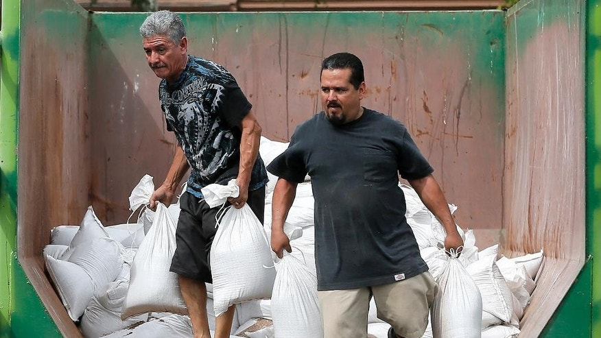 Julio Valenzuela Jr. and Julio Valenzuela Sr. take free sandbags to protect their homes, Tuesday, Sept. 16, 2014 in Mesa, Ariz. Phoenix area residents are filling sandbags in anticipation of the remnants of Category 3 Hurricane Odille which decimated Mexico's Baja California.   (AP Photo/Matt York)