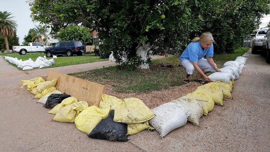 Gayle Peterson stacks sandbags to protect her home, Tuesday, Sept. 16, 2014 in Mesa, Ariz. Phoenix area residents are filling sandbags in anticipation of the remnants of Category 3 Hurricane Odille which decimated Mexico's Baja California. Odille's remnants are expected to hit Arizona in the coming days. P  (AP Photo/Matt York)