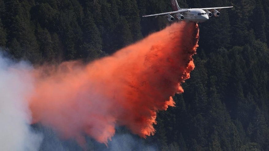 A jet aerial tanker drops its load of fire retardant on a fire near Pollack Pines, Calif., Monday, Sept. 15, 2014. The fire, which started Sunday has consumed more than 3,000 acres and forced the evacuation of dozens of homes. (AP Photo/Rich Pedroncelli)