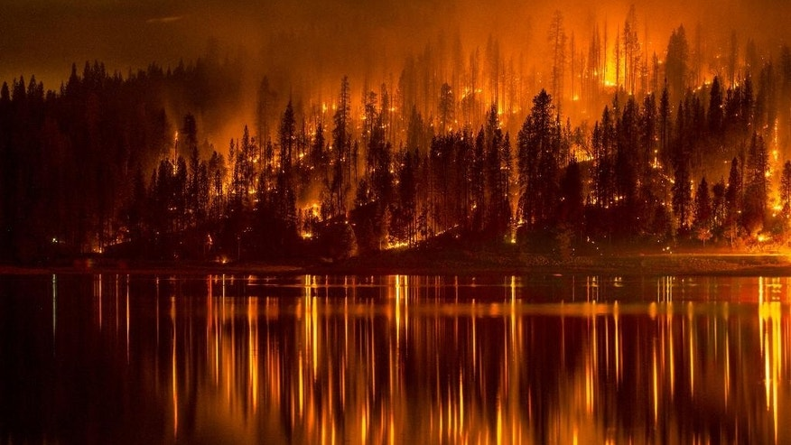 This Sunday, Sept. 14, 2014 photo shows fire as it approaches the shore of Bass Lake, Calif. Crews are attempting to get better access to two raging wildfires in California on Monday that have forced hundreds to evacuate their homes. (AP Photo/YosemiteLandscapes.com, Darvin Atkeson )
